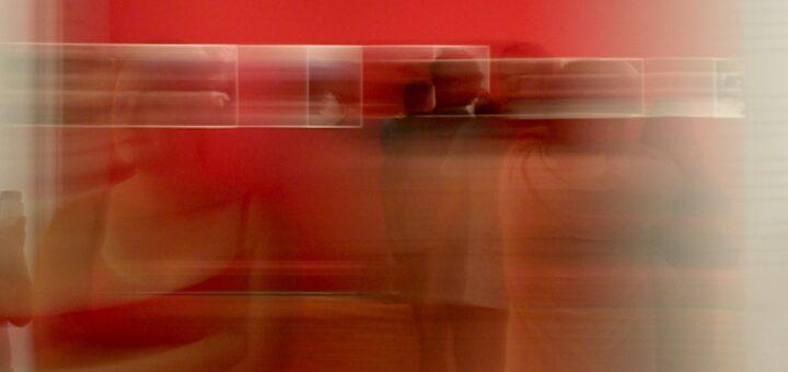 Die verschwommene Fotografie lässt eine Ausstellungssituation erahnen. An einer Wand hängen Bilder, schemenhaft sieht man Menschen davor stehen.