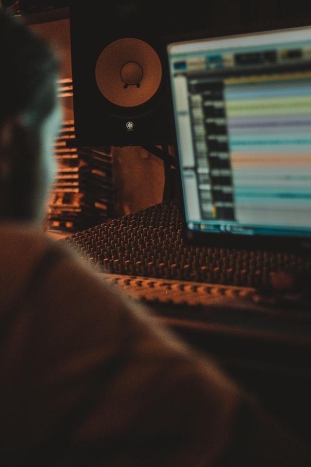 Eine Person sitzt vor einem Computer. Auf dem Bildschirm sind Samples zu sehen.