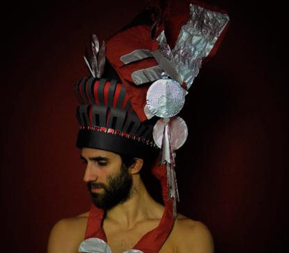 Das Schulterportrait zeigt einen Mann vor einem dunkelroten Hintergrund, der eine hohe, schwarz-rote Trachtenmütze trägt. Sie ist zweistöckig und hat als Krönung einen überragenden Aluminiumaufsatz. Auf beiden Seiten hängen rote Kordeln bis zu den Schultern.