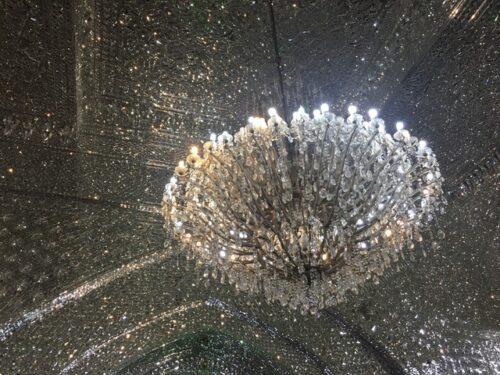Kronleuchter, der von einer ebenso prachtvollen, mit diamantenen Steinchen bedeckten Decke hängt.