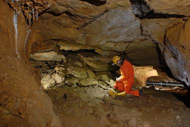 Yves Billaud  observant une zone d'entrée potentielle de la grotte (cliché St. Jaillet - EDYTEM)