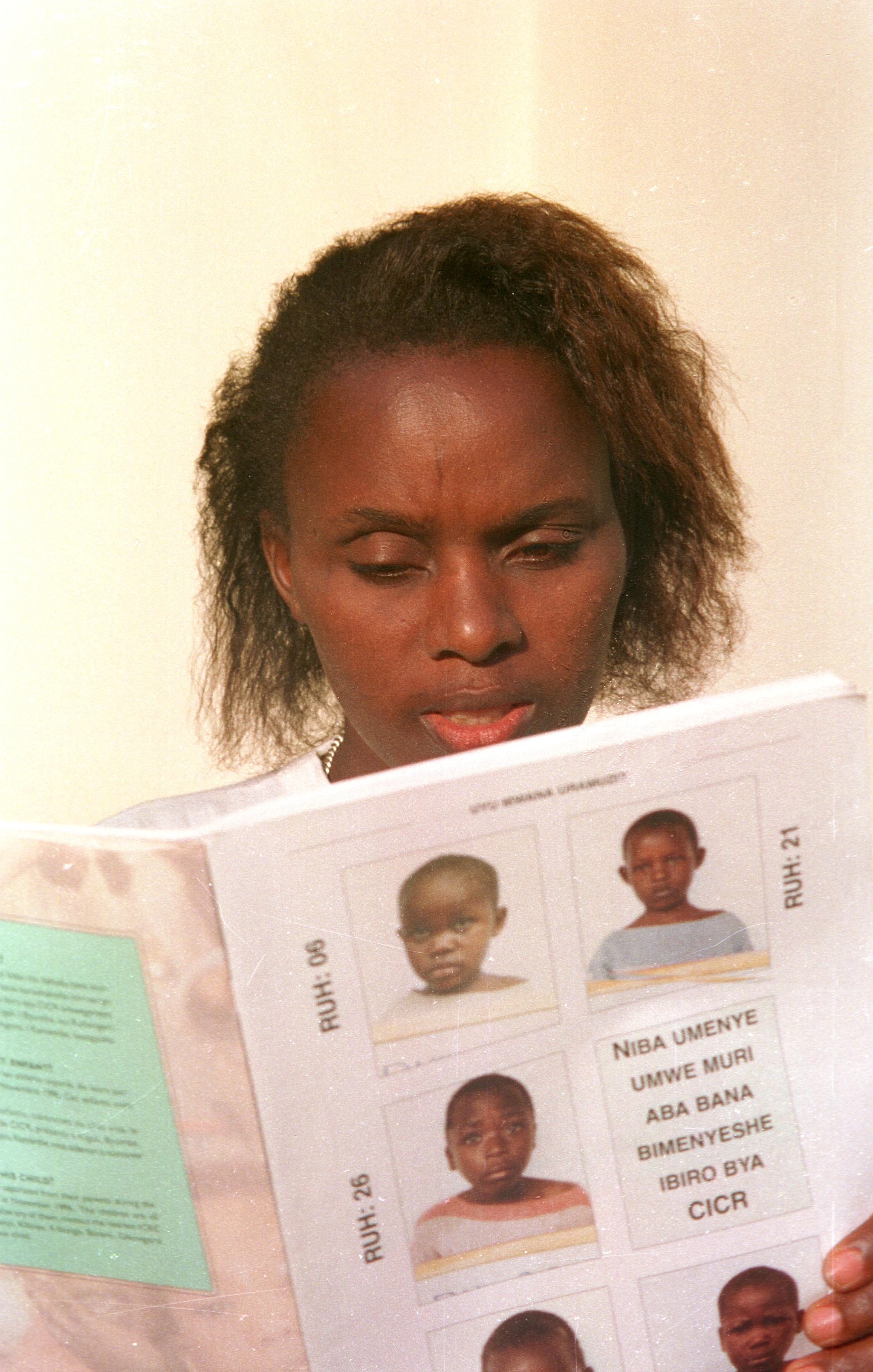 Bangui. Réfugiée rwandaise essayant d'identifier des enfants non accompagnés photographiés par le CICR. juin 99