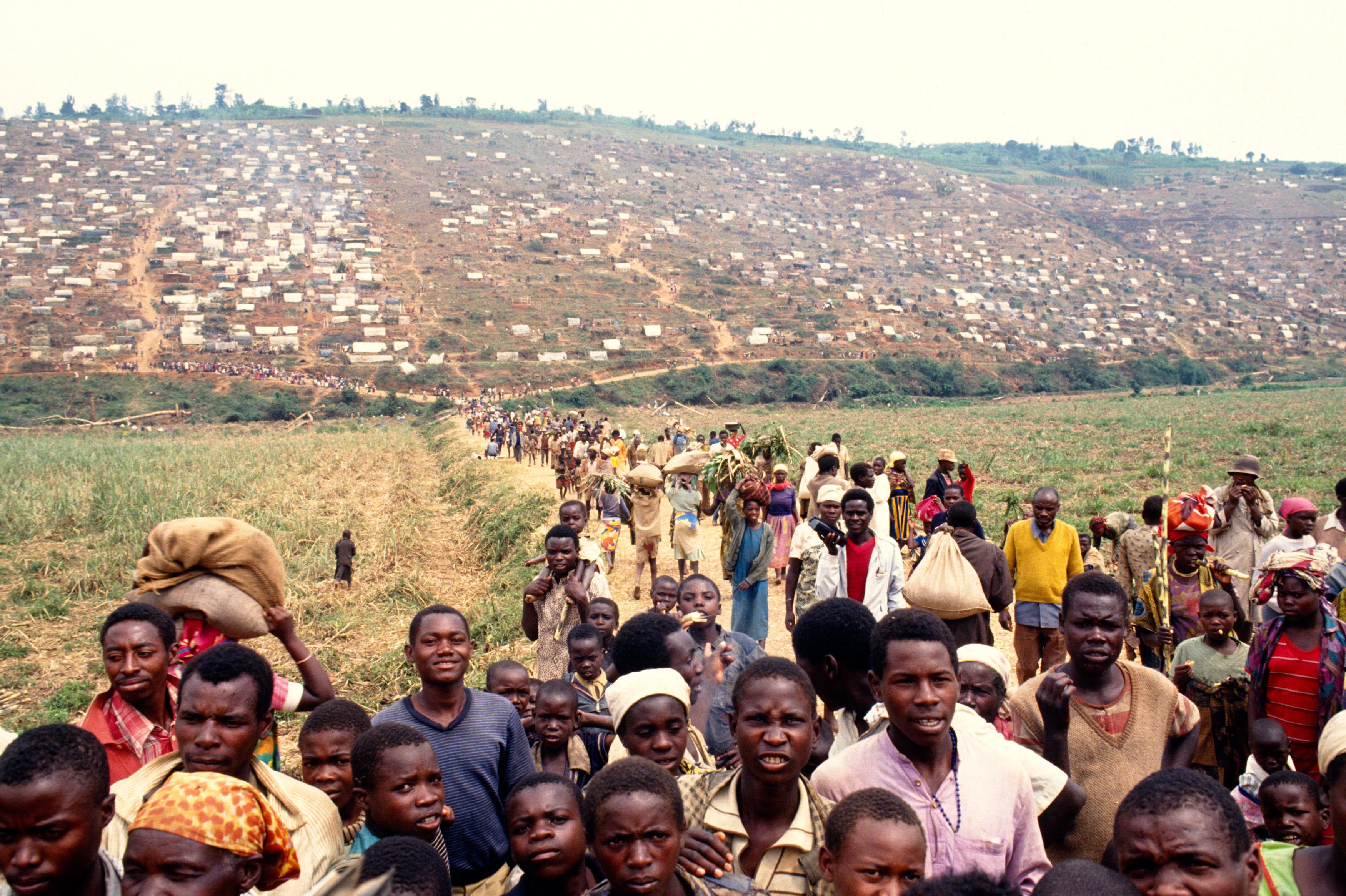 Nyacyonga. Camp de personnes déplacées. En une semaine, environ 30'000 personnes fuyant les combats, trouvent refuge dans et aux alentours du camp. Nyacyonga. Internaly displaced persons camp. In a week, about 30'000 personnes fleeing fights, find refuge in or around the camp. La famine menace environ un million de personnes déplacées, il faut au minimum 13'000 tonnes de vivres par mois pour les nourrir. Leur santé est gravement menacée par des conditions de vie très précaires (manque d'hygiène, promiscuité, sous-alimentation...)
