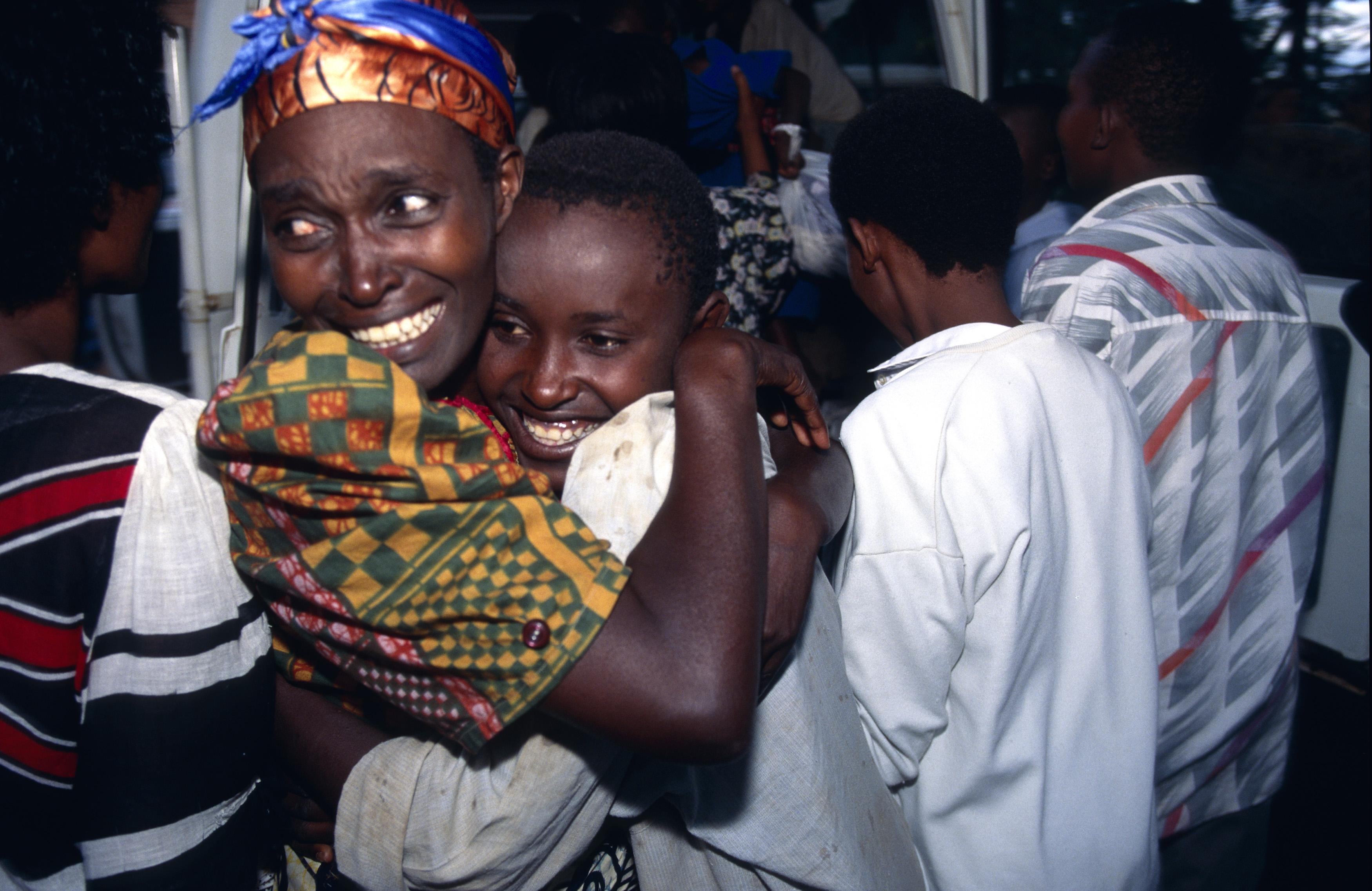 Kigali. Réunion de famille: étreintes de joie entre une femme et son enfant. Kigali. Family reunion under the aegis of the ICRC.