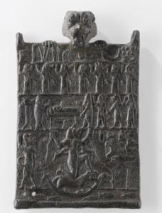 Amulette portée par Pazuzu dont on voit la tête qui dépasse la plaquette dans laquelle au centre en bas est représentée la démone Lamaštu (Musée du Louvre)