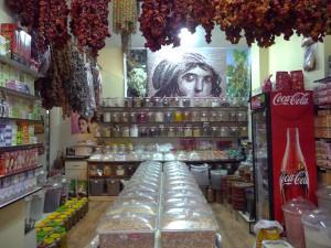 Intérieur de l'épicerie Baharat Dünyası. A la vente de produits directement importés de Gaziantep (pistache, salça, turşu, etc.) répond une décorationqui renvoie aux géosymboles gaziantepli (au fond, photographies de pistachiers et d'une des célèbres mosaïques de Zeugma) Cliché : P. Raffard, mai 2013