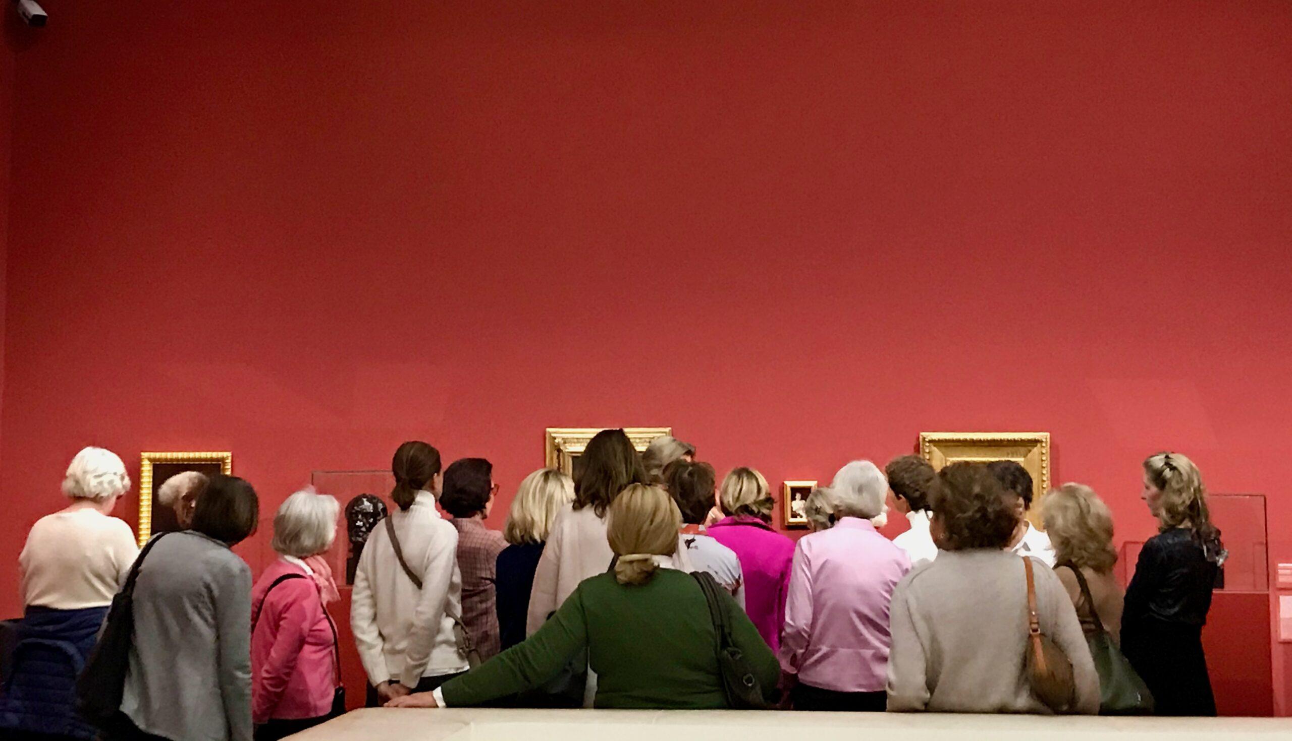 Na imagem vê-se o interior de um museu, um grupo de pessoas que se juntam numa visita guiada