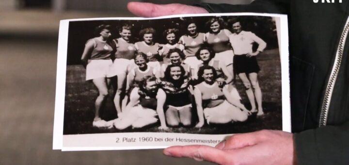 Zwei Hände halten ein schwarz-weiß Foto einer Mannschaft mit Handballerinnen