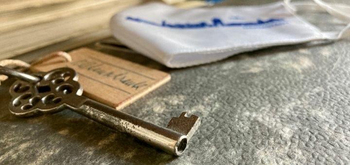 Ein Schlüssel liegt auf einem Aktenordner, im Hintergrund eine Alltagsmaske mit blauer Beschriftung
