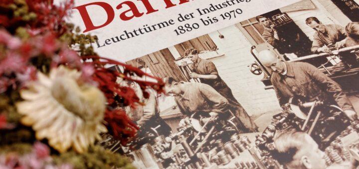 """Titelseite des Buchs """"Darmstadt. Leuchttürme der Industriegeschichte 1880 bis 1970"""", im Vordergrund ein Adventskranz"""