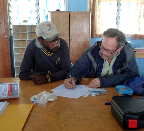 Matthew Leavesley recording anthropological data from a participant at Denglagu mission.