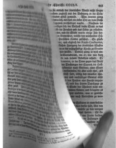 Image of a book page being scanned with the fingertip of the digitization technician visible.