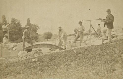 Ouvriers, tailleurs de pierres, travaillant à la construction d'un ponton à l'aide d'un coffrage, en présence d'un géomètre (vers 1888).