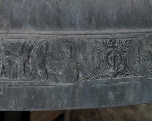 Fig. 12. Détail de la cloche Jeanne d'Arc : médaillon représentant Jeanne d'Arc à Rouen, trophées. Photo Éric Dessert © Région Rhône-Alpes, Inventaire général du patrimoine culturel, ADAGP, 2010