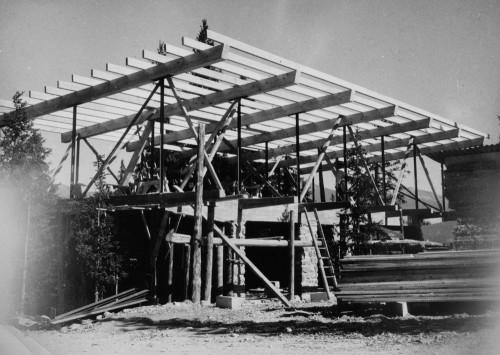 Charpente en cours de montage (pannes, arbalétriers, poteaux métalliques) reposant sur la maçonnerie en béton et en pierres, chantier en cours, été 1951