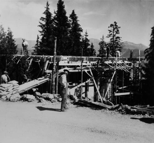 Maçonnerie en cours d'exécution (murs en béton et en pierres, dalle de béton, échafaudage et coffrages en bois), chantier en cours, été 1951