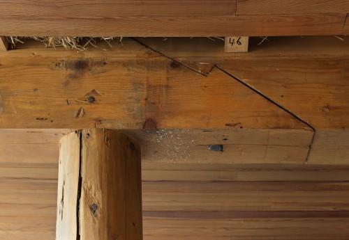 Détail d'assemblage de la charpente : l'arbalétrier en deux pièces de chêne assemblées par trait de Jupiter, repose sur un pilier bois circulaire ; en plafond, lambris de pin fixé sur des liteaux (dans la salle commune).