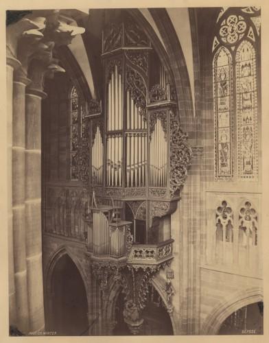 Prise avant le démontage par Koulen en 1892, cette photo de l'orgue Silbermann que l'on doit à Charles Winter montre quelques lacunes dans le décor sculpté, non réparées après le bombardement de 1870. En haut à droite du grand buffet, on distingue les tuyaux du récit, ajoutés en 1833 par Georges Wegmann (Fondation de l'Œuvre Notre-Dame, Strasbourg)