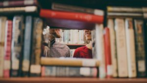 Couple smiling behind books, Berkeley Public Library