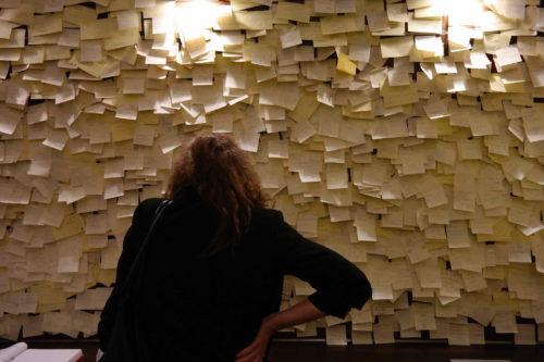 Na imagem vê-se uma parede totalmente coberta com post-it e vê-se uma pessoa de costas atenta à parede