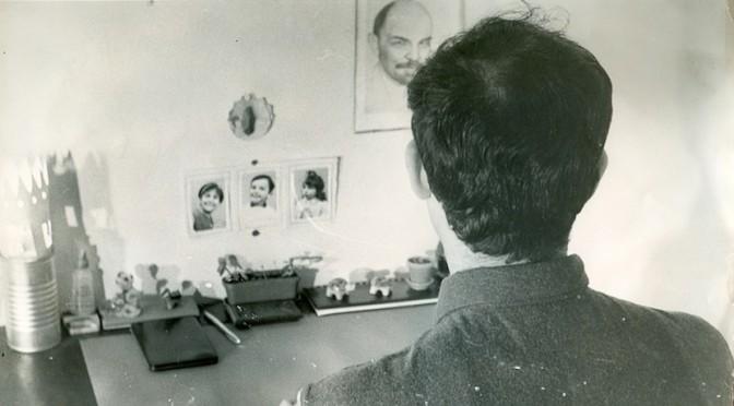 Sadek Hadjerès, photographié par un camarade en clandestinité en 1967, rue de Mulhouse, à Alger, tout près de la place Audin. La photo, prise de dos, pour des raisons de sécurité, est destinée à être envoyée à la famille. Au mur, les photographies des enfants, et le portrait de Lénine, Archives privées ©Inas éditions.