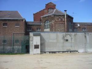A gauche, l'aile à dortoirs de 1860 ; au centre, le rond-point central avec les traces de l'aile bombardée ; au delà l'aile cellulaire, plus élevée, de 1910 ( photographie prise depuis le terrain de football)