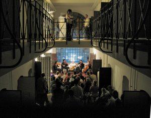 Fig. 22 : Concert dans l'espace central du Pénitencier de 1913 lors de la Nuit des musées en 2006: Métissages. La rencontre d'un guitariste et d'un quatuor à cordes © Musées cantonaux du Valais, Sion. François Lambiel