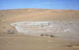 Le paléolac de Guern es Guesmia 1, au cœur du Grand Erg Occidental. Les dépôts, datés de 8800 à 7100 BP, suivent le versant abrupt du chaudron.