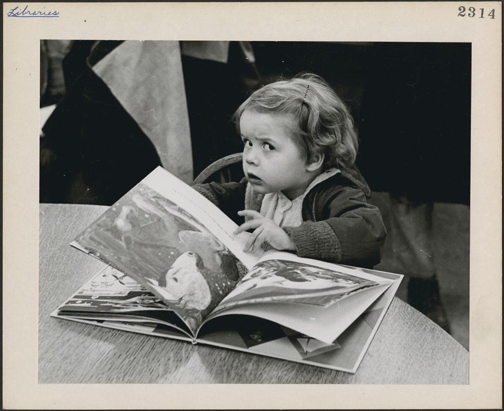 Une lectrice de trois ans, Jennifer Adair, lit dans une bibliothèque publique de Montréal (Québec) https://www.flickr.com/photos/lac-bac/albums/72157647002392007 . CC BY 2.0