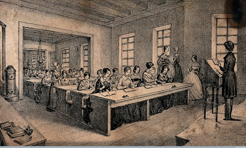 A classroom with children sitting at long tables and a teacher standing with a book in her hand. Lithograph J.B. Sonde. Credit: Wellcome Library, London.