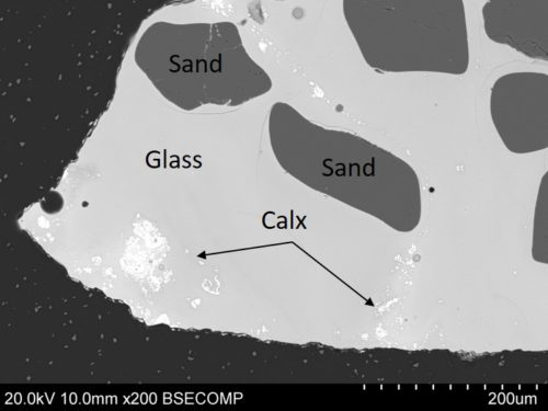 Figure 3. SEM image of residue A showing dark sand grains and remains of lead-tin calx used as opacifying agent.