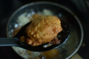 Black spoon with small fritter in it.