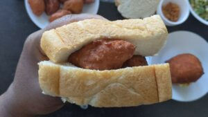 Hand holding sandwich made of white bread and fritters.