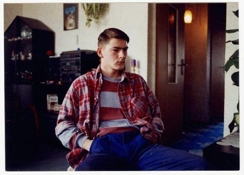 Ein Jugendlicher aus dem Film in seinem Wohnzimmer sitzend