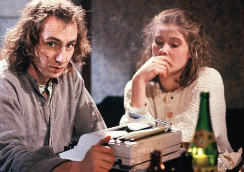Die Hauptdarsteller um eine Schreibmaschine sitzend.